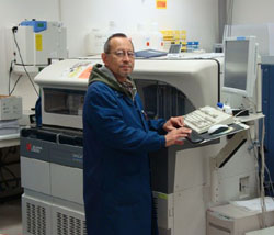 Photo of a chemistry technologist at work on a Beckman Coulter DXC600 Chemistry Analyzer