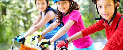 Children ride their bikes with helmets.