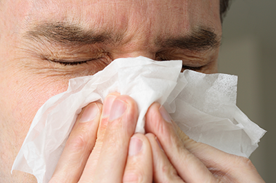 Man sneezing into tissue.