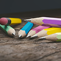 Differently colored pencils in a pile on a wooden table.