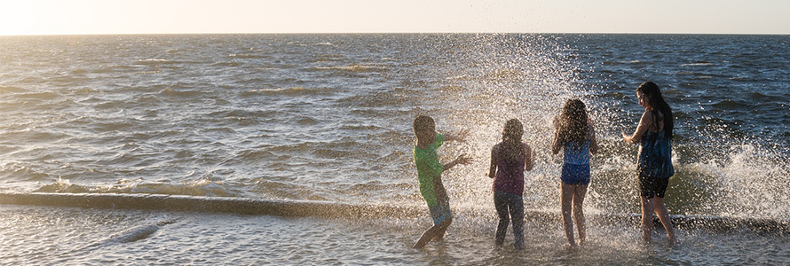 Four children play in the surf at the beach.