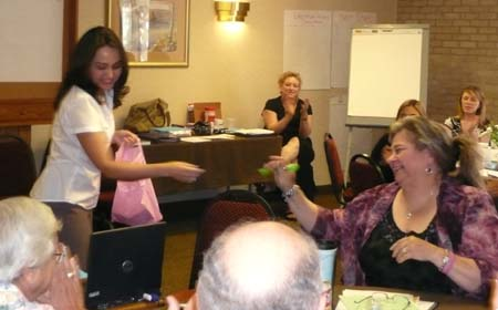 Photo of Mirsa Douglass giving a pen to Donna Claeys as a fun thank you for her help